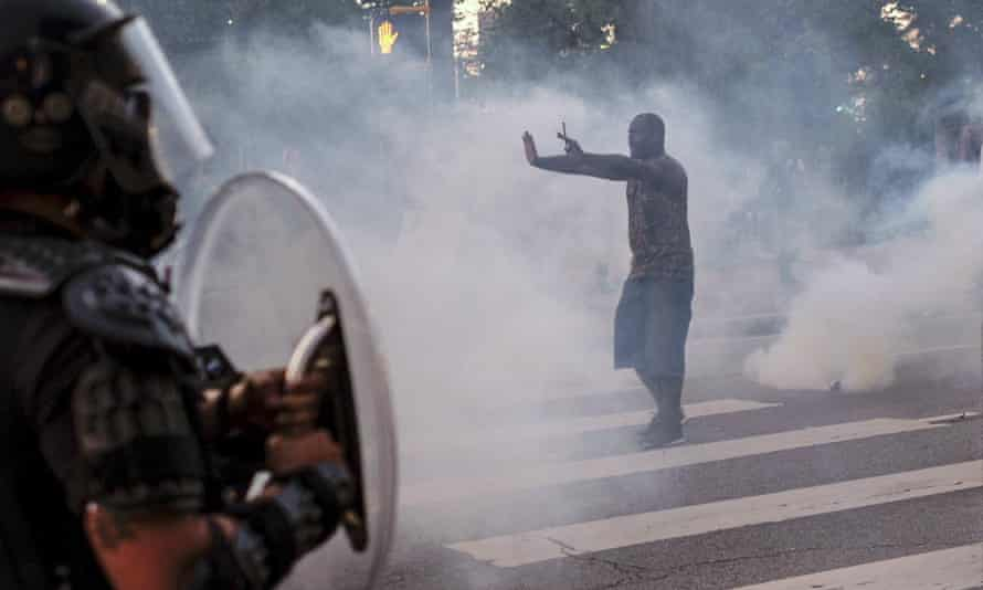 A protester tries to talk the police back amid teargas in downtown Atlanta on 25 May.