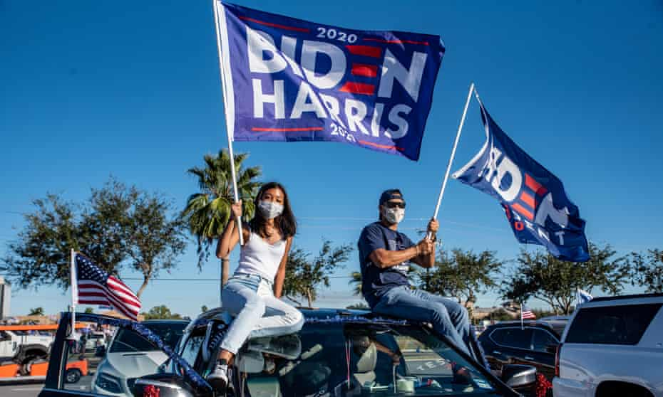 Attendees wave flags during a campaign event with Democratic vice-presidential nominee Kamala Harris in Edinburg, Texas, on 30 October 2020.