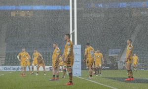 The Wasps players stand in the rain as Joe Simmonds of Exeter Chiefs takes a penalty just before half-time.
