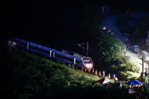 Rescuers inspect the train which derailed in a tunnel north of Hualien county in eastern Taiwan