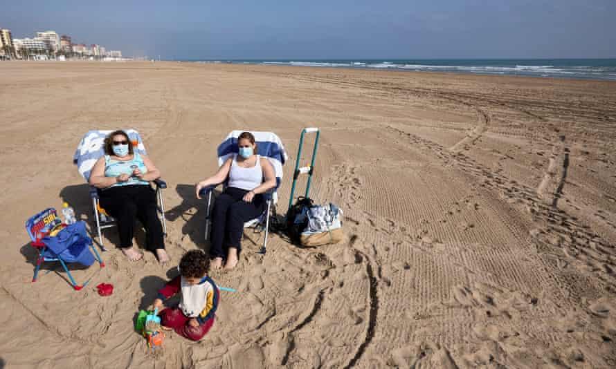 Women relax on a beach in Valencia, Spain