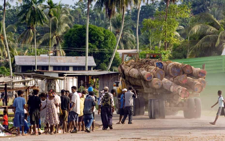 Un camion forestier circulă prin satul Vanimo, Papua Noua Guinee, în drum spre Vanimo Forest Products Camp, unde cheresteaua va fi încărcată pe o navă pentru export în China.