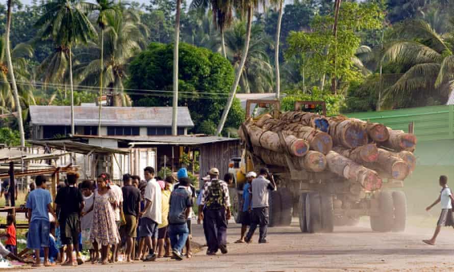 a logging truck passes through the village of vanimo, papua new guinea