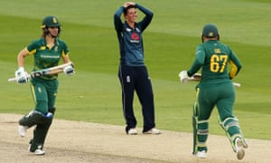 Elwiss of England looks dejected as Laura Wolvaardt and Lizelle Lee of South Africa run between wickets.