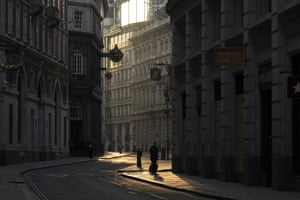 City of London, UK: a woman walks through the deserted streets at sunrise