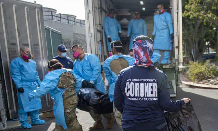 Officials and national guard members place bodies into temporary storage at the LA county medical examiner-coroner office last week.