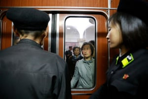 Commuters are photographed through a door as they wait to board a train in Pyongyang.