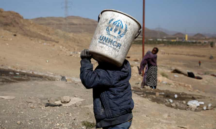A displaced Yemeni boy carries a UNHCR bucket at a camp for Internally Displaced Persons (IDPs) on the outskirts of Sana'a, Yemen, 1 March 2021.