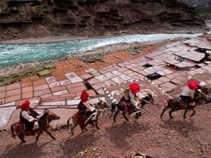 Khampa horsemen riding by the salt pans of the Lancang river on the Tibetan plateau