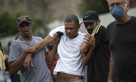 Alexsandro dos Santos, center, is helped by friends during the burial of his four-year-old daughter Emily Victoria Silva dos Santos/
