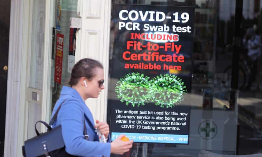 A woman walks past a sign on a pharmacy window  offering Covid-19 PCR swab tests