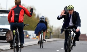 Boris Johnson waves away a fellow cyclist's hand gesture as he opens the first cycle superhighway in London.