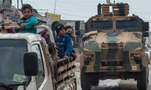 Displaced Syrians and a Turkish military armoured vehicle in Idlib, Syria.
