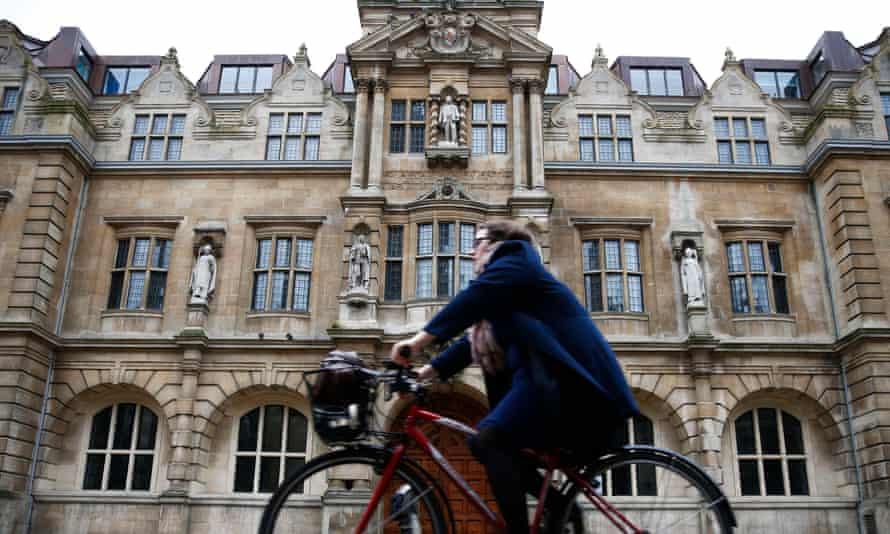 woman rides bike past Rhodes statue at Oriel College, Oxford