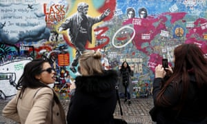 Tourists pose near a painting of Václav Havel on the Lennon wall.