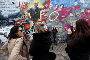 Prague, Czech Republic. Tourists pose by newly created graffiti