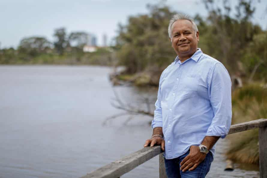 Noongar artist Barry McGuire stands on the banks of a river