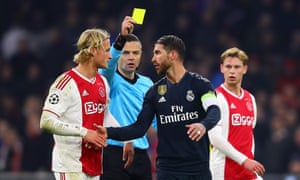 Sergio Ramos is booked for a foul on Ajax's Kasper Dolberg.