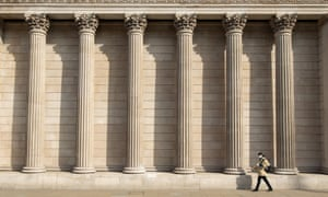 A woman in a face mask walks past the Bank of England