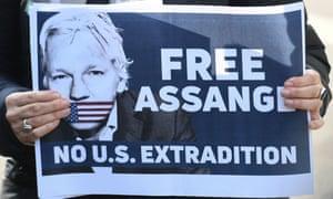 German Die Linke MP Heike Hansel holds a placard calling for freedom for WikiLeaks founder Julian Assange at Belmarsh Prison in London