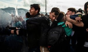 Scuffles have broken out between migrants and riot police on Lesbos amid a surge from Turkey after it opened its borders to thousands of refugees trying to reach Europe.