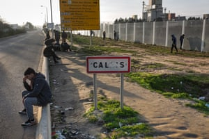 Migrants wait by the roadside in Calais