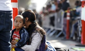 A woman sits with her sons as they wait to apply for asylum in the US along the border in Tijuana, Mexico. on July 2019.