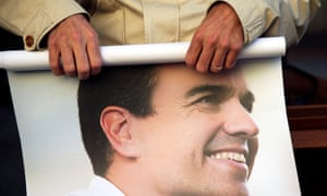 A supporter holds a poster of Pedro Sánchez.