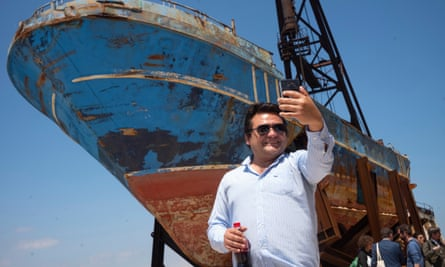 A man takes a selfie in front of Barca Nostra, exhibited at the Venice Biennale