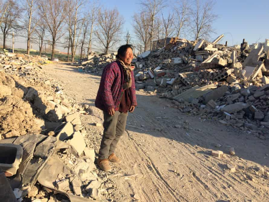Zheng Yuzhi, a migrant from Shandong, has dug a shelter in the ground after losing her home.