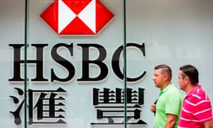 Pedestrians pass an HSBC sign in Hong Kong.