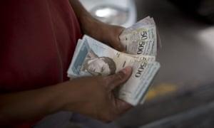 A employee accounts bolivar bills at a petrol station in Caracas, Venezuela.