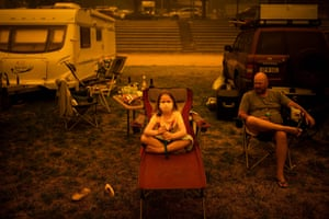 Amy and Ben Spencer sit at the show grounds in the southern New South Wales town of Bega where they are camping after fleeing wildfires.