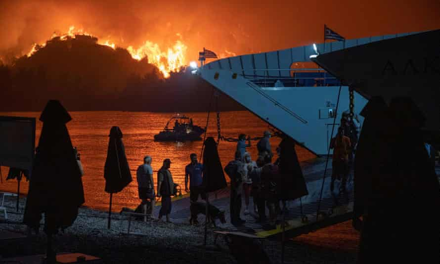 People board a ferry during evacuation as a wildfire burns in the village of Limni, on the island of Evia, Greece, on Friday.