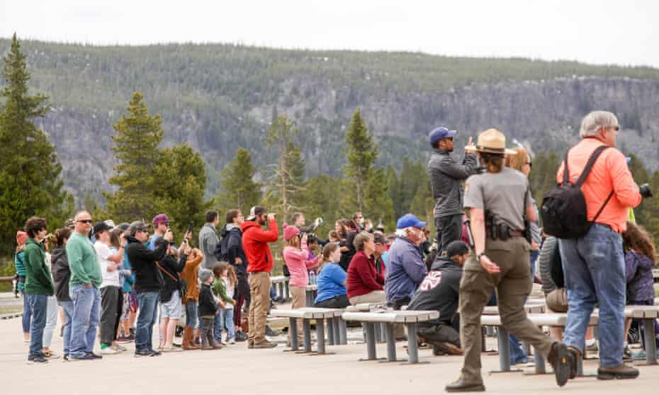 Visitors watch Old Faithful erupt on Monday afternoon on Yellowstone national park's opening day.