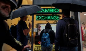 People watch the currency exchange values in the buy-sell board of a bureau de change in downtown Buenos Aires