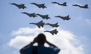 A man watches Russian military jets performing in Alabino