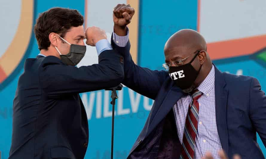 Jon Ossoff and the Rev Raphael Warnock bump elbows on stage during a rally with Joe Biden in Atlanta, Georgia, on 4 January.