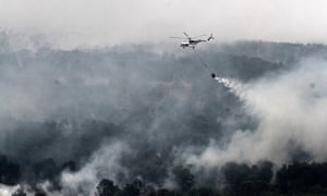 A MI-17 helicopter run by the Indonesian National Disaster Mitigation Agency water-bombs a fire in South Sumatra province
