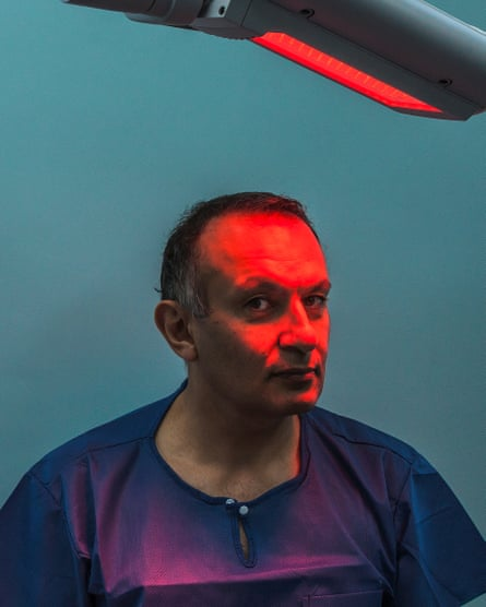 Dr Bav Shergill - Consultant Dermatologist - with a red light shining on his face