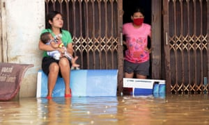 Women look out from a flooded house in the southern Thai village of Chauat on January 7, 2017. Heavy rains continued to hammer Thailand's flood-ravaged south on January 7, bringing the death toll up to 12 and leaving thousands of villages partially submerged, authorities said. / AFP PHOTO / TUWAEDANIYA MERINGINGTUWAEDANIYA MERINGING/AFP/Getty Images