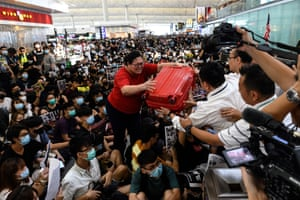Hong KongA tourist gives her luggage to security guards as she tries to enter the departures gate during another demonstration by pro-democracy protesters at Hong Kong's international airport.