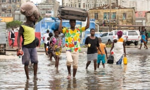 People carry their personal effects through a flooded section of Praia Nova, Beira, Mozambique, after Cyclone Idai caused catastrophic damage