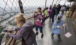Visitors enjoy the view from top of the Eiffel Tower in Paris