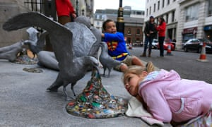 A sculpture of a seabird regurgitating rubbish and a young girl crouching down trying to see in its mouth