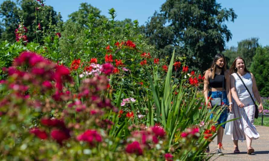 Two women walk among flowers in Hyde Park, London