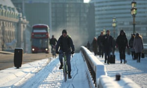 A cyclist crosses Westminster Bridge in the snow, London, 28 February