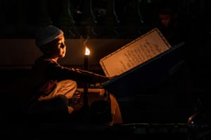 A boy reads by torchlight in Yogyakarta, Indonesia