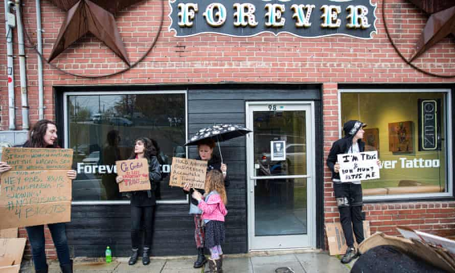 Protesters stand outside Forever Tattoo in Asheville, North Carolina, on Thursday,.