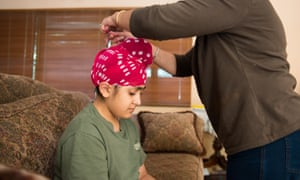 Kuljeet Kaur drapes a 'patka' (head covering) around her 10-year-old son Simran's head. Sikhs believe that keeping one's hair is a sign of accepting what God has given.